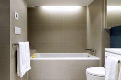 Falken Reynolds - Howe St. Apartment - www.falkenreynolds.com Tiled bathtub with LED cove lighting and minimal & linear lines