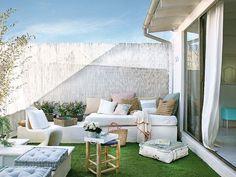 Terraza, con un sofá de obra, un jacuzzi y césped sintético en el suelo, evoca las casas de la playa