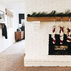 Christmas decor, stockings, garland, mantle, white brick, fireplace, midcentury modern