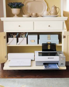 A hutch or sideboard can be quickly retrofitted to accommodate all your office essentials. Silverware caddies, painted to match the hutch's exterior, organize pens, scissors, and a stapler and can be carried to the table when needed. A pull-out shelf made with drawer glide hardware ensures hassle-free access to the laptop and printer. Cords are kept out of sight by a concealed surge protector (situated behind the computer).
