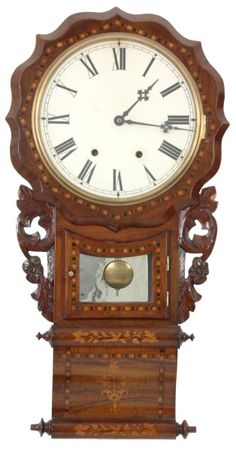 """Inlaid Ansonia English Drop Wall Clock. 12 in. replaced paper dial with large black Roman hour numerals, fancy pierced blued hands and hinged door bezel; pierced brass 8 day spring driven movement signed """"Ansonia Clock Co., Ansonia, Conn."""" has an hour countwheel strike on a bell. In an inlaid walnut case with wavy pie crust top, pierced carved filigree side corbels, glass lower door panel with mirrored back, fancy turnings in the lower bracket with finials; in nice condition with a French…"""