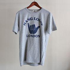 """英国ブランドYMCの""""Hang Loose London!"""" Tシャツ。 Hang Looseとは、""""ゆったりと行こう!""""、""""気楽に人生を楽しもう!""""というニュアンスを持つ言葉。カラーはグレーにネイビーのグラフィックプリント。素材は、コットン100%です。"""