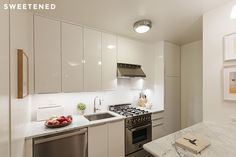 Greenwich Village kitchen with custom Carrara marble countertops, white lacquer IKEA cabinets, Blanco sink, Miele dishwasher, and Bertazzoni stove range.