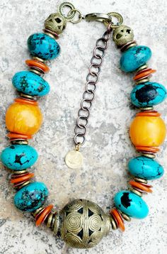 "African-Inspired Turquoise, Amber, Yellow and Bold Brass Ball Choker. Materials: Chinese turquoise stones. Ornate brass focal bead from Ghana. Orange glass discs. African brass rings. Copper discs. Yellow amber resin. Beaded brass rings.Length: 17"" + 4"" extender. $325.00 USD. At: http://www.xogallery.com"