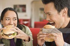 Asian couple eating hamburgers