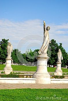 Photo made in Prato della Valle in Padua in Veneto (Italy). In the image, taken from the outside of the island Memmia, it is seen in the foreground the statue pointing towards the target with his arm raised to the sky, behind and on either side are placed two statues which look over the green grass, the trees and the blue sky.