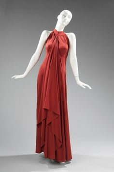 "Via The Costume Institute of The Metropolitan Museum of Art  ""Here… she uses silk crepe to create soft drapery; the center front panel falls in an eye-catching cascade of folds; or if desired, the panel can be wrapped around the body in the style of a himaton, an ancient Greek shawl-like cloak worn by women, similar to the chlamys worn only by men."""