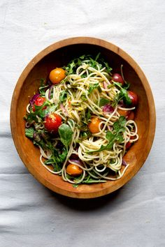 Roasting garlic scapes with tomatoes and red onion sweetens them and enriches their flavor; toss them with pasta, lemon juice, and arugula for a simple summer meal.