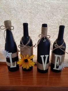 set of four recycled wine bottles painted black and hand decorated with love. Made with twine, flowers, charm and wooden letters. These would make the perfect wedding for that special couple. Wine Bottle Glasses, Wine Bottle Art, Diy Bottle, Bottle Lamps, Recycled Wine Bottles, Painted Wine Bottles, Diy Projects For Couples, Wine Bottle Centerpieces, Pots