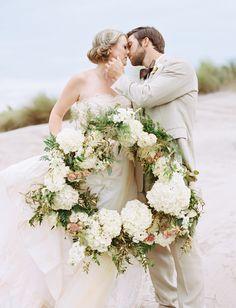 Beautiful Shot of the Bride and Groom on the Beach with a Wreath #wedding #southernwedding #beachwedding