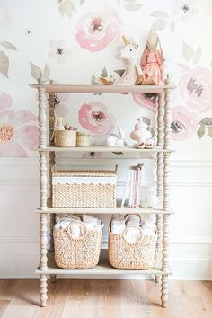 Pretty changing station ideas for the nursery. Pink floral wallpaper in the nursery compliments this well organized changing table for baby.