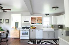 Simple, affordable kitchen update. Cabinets painted; vinyl floors swapped to plank laminate; drop-in stainless steel sink replaced with an apron farmhouse sink; laminate countertops upgraded to solid surface. The before can be found here.