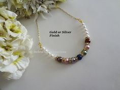 """This birthstone necklace consists of up to 12 birthstones and Your Choice of Cream, Cream Rose or White Base Pearls, Gold Plate or Silver Plate Crystal Rondelle Spacer Beads, Round Metal Beads, Cable Chain as well as Gold Plate or Silver Plate Lobster Clasp, Wire Guards and Components. The necklace comes in 16"""" and 18"""" with the option of a 2"""" chain extender. The total pearl piece measures 6.00."""""""