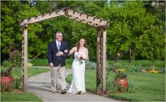 Bride laughs with her dad as they walk down the aisle under the wood arch at Denver Botanic Gardens Chatfield Farms in Colorado. - April O'Hare Photography http://www.apriloharephotography.com