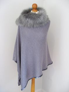 Faux fur trimmed poncho with sequins at hem.