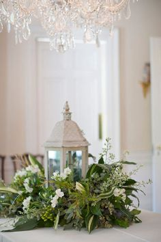 Lovely green and white florals surrounding a white lantern. Add a candle for a beautiful effect.