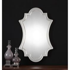 The Atley Mirror features a sophisticated shape with etched accents and a classic broken silver leaf-finished metal frame.