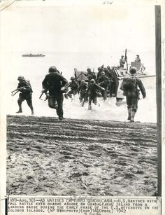 1942- Members of the U.S. First Marine Division charge ashore on Guadalcanal from a landing barge.