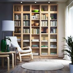 A reading corner with BILLY bookcases in birch veneer, POÄNG armchair in birch and white and a chequered green STOCKHOLM rug