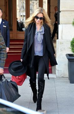 Kate Moss looked chic in a blue and white print bow neck blouse and a long white coat.