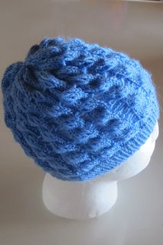 Knitted beanie - Adeline Cable & Eyelet Hat using a plain blue acrylic yarn.  Pattern can be found at  http://www.ravelry.com/designers/grace-rose