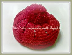 Cappello a uncinetto rosso con pompon realizzato con filato 50% lana 50% acrilico