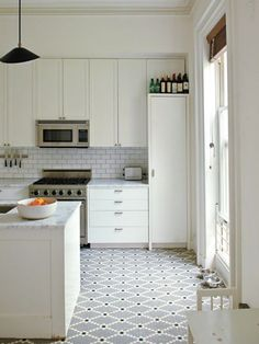 updating white kitchens - all white kitchen with patterned mosaic dot bistro style floor - design sponge at home via atticmag
