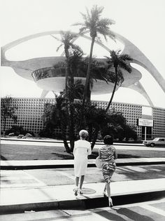 With his trademark tilted horizon, Garry Winogrand's photograph of two women in front of the Theme Building by architects William Pereira, Paul R. Williams, Charles Luckman, & Welton Becket | Los Angeles International Airport (LAX)