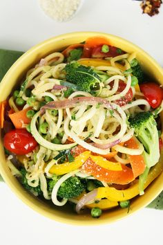 Zucchini Pasta Primavera - broccoli florets, olive oil, minced garlic, red pepper flakes, cherry tomatoes, red onion, green peas, bell pepper, salt & pepper, chopped parsley, zucchinis, carrots, lemon juice, grated Parmesan cheese