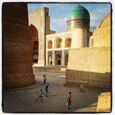 A Bukhara i bambini giocano in strada ai piedi del Minareto Kalon. Sullo sfondo la Madrasa di Mir Arab. Photo by Riccardo Negro - Walter Viaggi