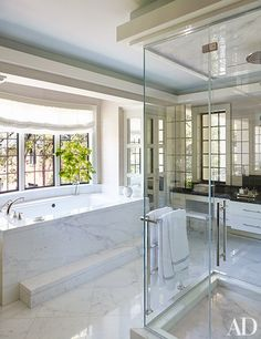 A bright master bathroom lined in Calacatta marble | archdigest.com