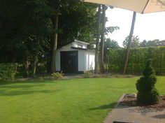Unter den großen Bäumen steht in diesem Garten ein Pultdach Gartenhaus in Weiß und Schwarz.