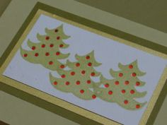 Holiday cards, Shiny red paper behind hole punched trees.