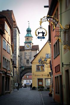 Colorful shops with unique signs and a clock tower along a street in Rothenburg, Germany