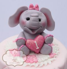 This custom-made fondant elephant cake topper holds a little heart with age or initial and is perfect for your 6 or 8 cake! (This listing is for Topper ONLY, cake is an example of what can be done with it.)  Approximately 4 tall (easily customized)  Want this in a different color palette? Want a differnt size? Want to add a plaque, or quilted pad under the elephant, or some flowers? Id love to customize this for you! Just message me!  Fondant toppers and plaques are food safe, but are meeant…