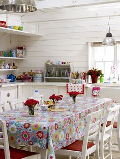 I love these colors for the kitchen: red with a flowery print tablecloth of blues, reds, yellow & white. So summery!