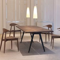 Welles table makes generous use of solid wood with an elegantly simple form. The tabletop, detailed with a central divide and angled edges, is set upon cast iron legs. This table is quietly functional while remaining approachable and appealing to the senses.