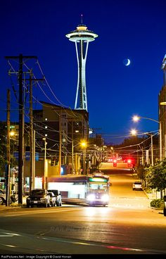 """An outbound Seattle Streetcar service swings around the corner from Westlake onto Thomas in Seattle's South Lake Union neighborhood. The iconic Space Needle dominates this blue hour scene, its roof having been repainted """"Galaxy Orange"""" to match the original appearance of the structure during 2012's 50th anniversary celebrations."""