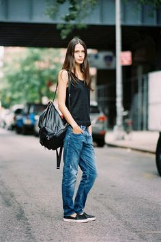 Jeans with slip ons, a black tank, and a backpack.