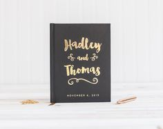 A beautiful wedding guest book in a fun, modern brush script printed with real gold foil, this minimalist design featuring an understated black and gold color theme is an instant classic that works well for formal or laid back weddings. The foil adds just the right amount of decoration without being overwhelming. The hardcover book can also be used as a wedding album or scrapbook (the pages are acid free), personalized with your first names in your choice of cover and foil colors. Shown here…