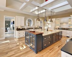 Just beautiful! Hickory wood flooring keeps it light and bright in this kitchen. & love the contrast of the blue island.