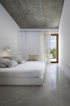 White walls, white furnishings, cement ceiling & flooring. Nice and Clean.