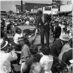 Original black and white photographic print taken by Frank Muto, showing Senator John F. Kennedy greeting supporters at Main and Center streets in Grand Prairie, Texas, during the 1960 presidential campaign.
