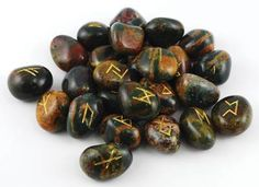 This handcrafted Bloodstone rune set beautifully displays the 24 runes of the Elder Futhark and one blank stone, accented with gold lettering, for your divination and magic. Stones can vary in size from -