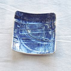 Somewhere for him to dump the contents of his pockets at the end of a busy day. This sturdy square man bowl has been impressed with an old pair of jeans capturing the rivets, creases, stitching and fine details then glazed in denim blue. Useful valet tray for keys, coins and mans stuff. Hand formed in white porcelain clay. 150 mm square approx. Food, microwave and dishwasher safe. Ready to ship within 3 working days. Each impression is unique and each glaze is unique. Yours will be just as…