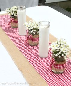 Cute jars with wrapped burlap, red/white gingham ribbon tied around it, and pretty little white flowers for table decorations.