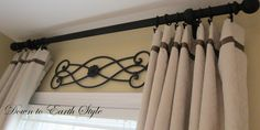 "Love the curtains featured on ""Down to Earth Style""! Holly said: ""These neutral panels were from Target but to make them look more custom we used Stitch Witchery to iron on some ribbon (no sew is the way to go)."" And love the iron scroll accent!"