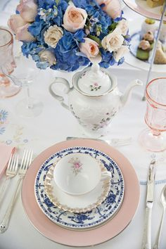 Light pink + blue wedding place setting idea - pink chargers with white + blue china plates + pink glasses displayed with blue + pink floral arrangements Photo by Pure Plush Photography
