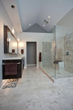 AFTER: A once-cluttered vanity area now has one dark-stained maple floating vanity with a light glowing over restful rocks underneath. A clear glass shower stall continues the streamlined effect