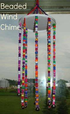 Using a recycled plastic lid, some yarn, pony beads and bells you can create this pretty wind chime to hang on your deck or from a tree outside. This would be cute hanging in a child's bedroom as well!